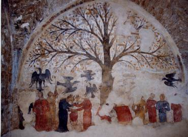 A photo of a medieval mural in Massa Marittima (province of Grosseto, region of Tuscany), Italy. Its main feature is a tree, some birds, and some women. The tree is laden with male genitalia.